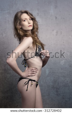 provocative female in sexy pose with long wavy hair and stylish swimsuit looking in camera  - stock photo