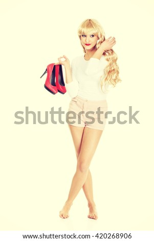 Provocative woman holding her high heels. - stock photo