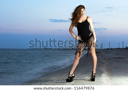Provocative young curly brunette showing her perfect figure on the beach at sunset