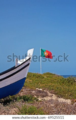 Prow of a fishing wooden boat. The portuguese flag, the blue sea and sky as background - stock photo