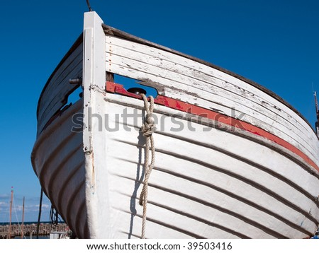 Prow of a small wooden boat with clear blue sky background - stock photo
