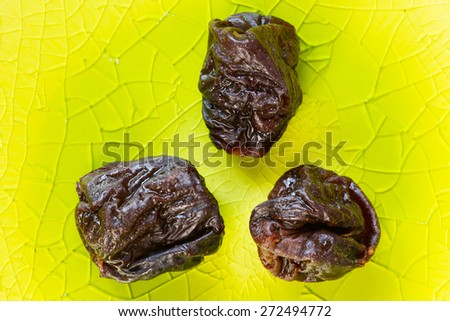 Prunes on a green plate - stock photo