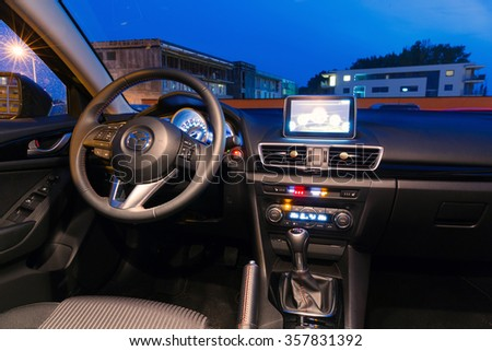 PRUSZCZ GDANSKI, POLAND - SEPTEMBER 24, 2014: Interior of new Mazda 3 captured at dusk with long exposure technique. Mazda 3 is a popular compact car manufactured in Japan. - stock photo