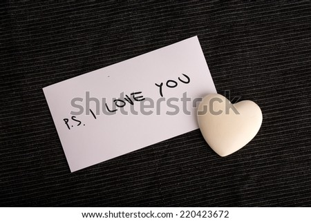 PS. I Love You handwritten on a white card with a cream colored heart symbolic of love and romance lying on a black background for a Valentines or anniversary greeting or a message to a loved one. - stock photo