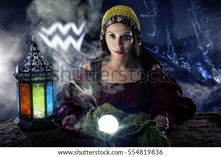 Psychic or fortune teller with crystal ball and horoscope zodiac sign of Aquarius, birthdays of January to February. The image depicts astrology in a mystical, esoteric or magical theme composite.