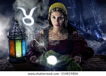 Psychic or fortune teller with crystal ball and horoscope zodiac sign of Taurus, birthdays of April to May. The image depicts astrology in a mystical, esoteric or magical theme composite.