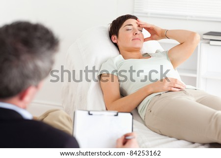 Psychologist talking to a depressed patient in a room - stock photo