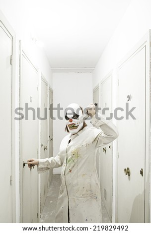Psychotic clown inside hospital, Halloween - stock photo