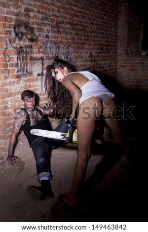 Psychotic woman with a chainsaw covered in blood - stock photo