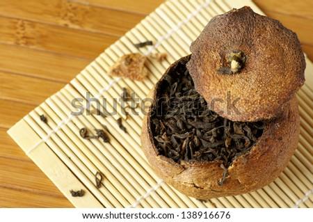 Pu-erh tea aged in tangerine on bamboo background. - stock photo