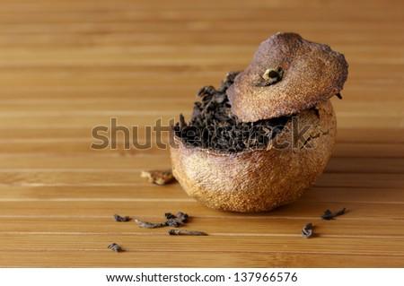 Pu-erh tea aged in tangerine on bamboo background. Shallow DOF. - stock photo