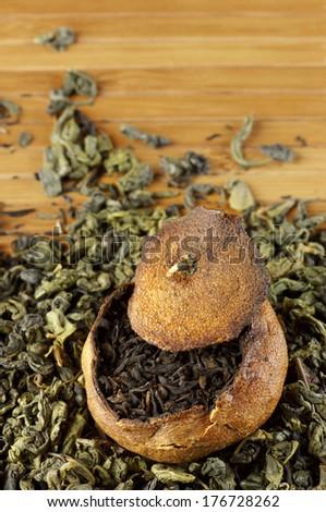 Pu-erh tea aged in tangerine on pile of green tea. - stock photo