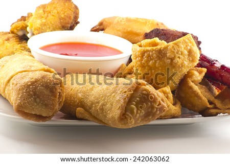 Pu pu platter with crab rangoon, egg rolls, fried chicken, BBQ Beef sticks, and fried wontons with sweet sauce - stock photo
