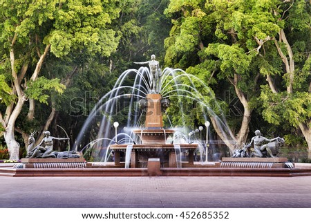 Public central city park of Sydney - Hyde park around Archibald fountain surrounded by tall green trees.