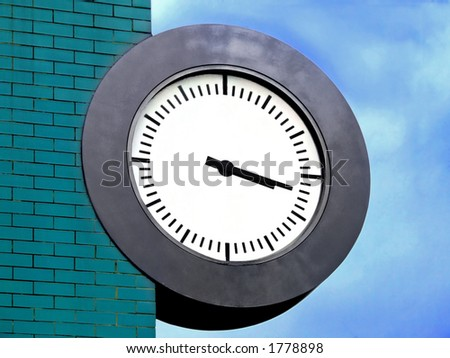 Public clock on the edge of turquoise brick wall - stock photo