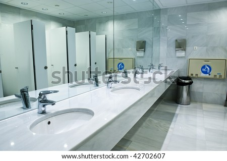 Public empty restroom with washstands, baby changer, and toilets in mirror - stock photo