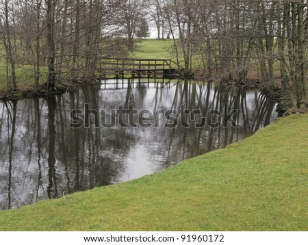Public golf course on a winter day without snow, northern Illinois: Bend in stream reflecting bare trees by footbridge - stock photo