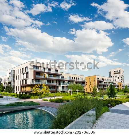 Public green park with modern blocks of flats and blue sky with white clouds - stock photo