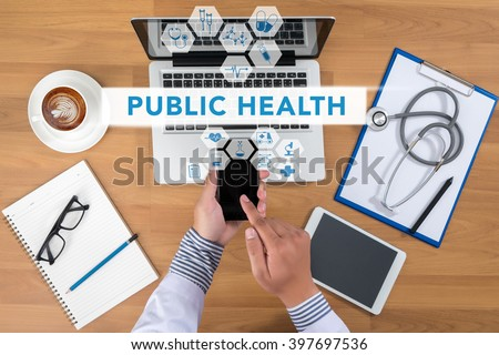 PUBLIC HEALTH CONCEPT   Doctor working at office desk and using a mobile touch screen phone, computer and medical equipment all around, top view, coffee - stock photo