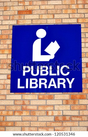 Public library sign displayed on a wall outside.
