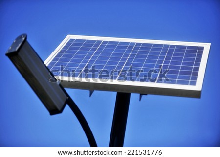 Public lighting pole with photovoltaic panel and blue sky on the background