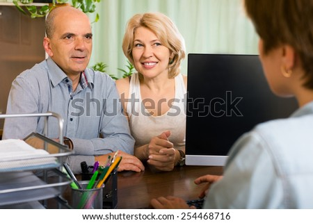 Public notary helping happy senior couple to make a will in office - stock photo