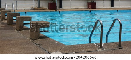 Public pool with clear blue water, stand for jump and see a ladder for access to the swimming pool.