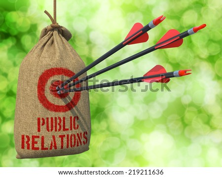 Public Relation - Three Arrows Hit in Red Target on a Hanging Sack on Green Bokeh Background. - stock photo