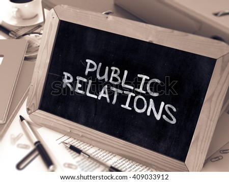 Public Relations Handwritten by White Chalk on a Blackboard. Composition with Small Chalkboard on Background of Working Table with Office Folders, Stationery, Reports. Blurred, Toned Image. 3D Render. - stock photo