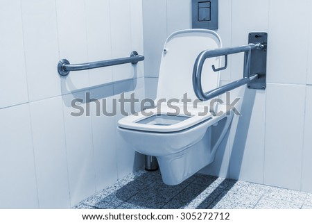 Public toilet cubicle for the disabled. Focus on the toilet - stock photo