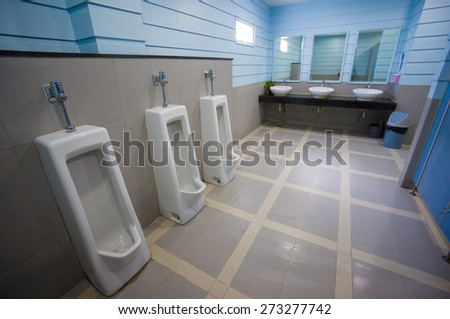 Public toilet with pissoirs and sinks in blue colors - stock photo