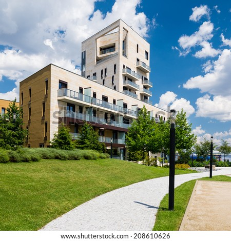 Public view of contemporary block of flats in green park with blue sky and white clouds above - stock photo