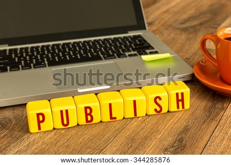 Publish written on a wooden cube in a office desk - stock photo