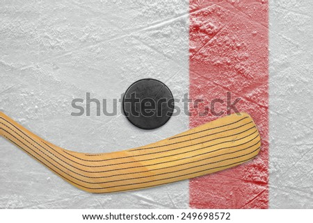 Puck and stick on the red line hockey rink. Texture, background - stock photo