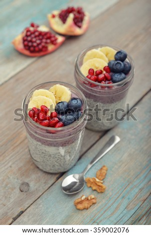 Pudding with chia seeds, yogurt and fresh fruits in glass jars on wooden background
