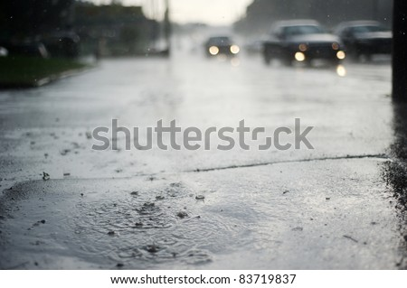 Puddle near the wet road in the rain - stock photo