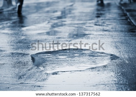 Puddle of water in rain - stock photo