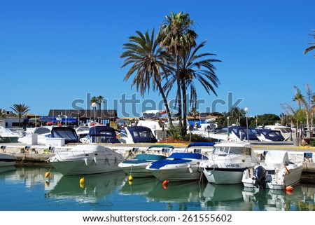 PUERTO CABOPINO, SPAIN - JUNE 7, 2009 - Boats in the inner harbour with restaurants to the rear, Puerto Cabopino, Costa del Sol, Malaga Province, Andalusia, Spain, Western Europe., June 7, 2009. - stock photo