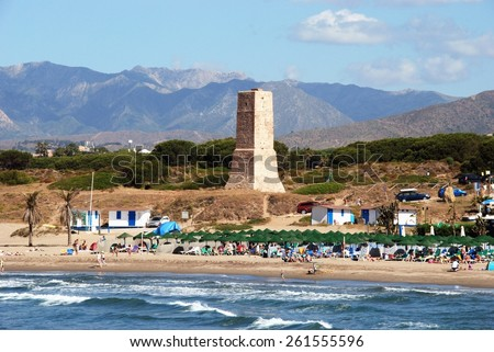 PUERTO CABOPINO, SPAIN- JUNE 7, 2009 - View of the beach with the watchtower and mountains to the rear, Puerto Cabopino, Costa del Sol, Malaga Province, Andalusia, Spain, Western Europe, June 7, 2009. - stock photo