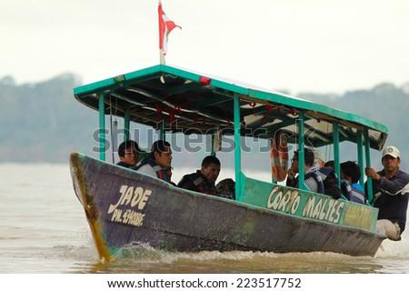 PUERTO MALDONADO, PERU - CIRCA 2013: A boat with people navigate the Madre de Dios river circa 2013 in Puerto Maldonado, Peru. - stock photo