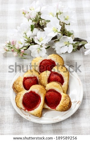 Puff pastry cookies in heart shape filled with strawberries. Blooming apple branch in the background - stock photo