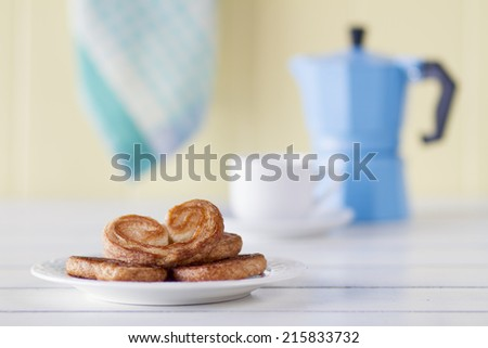 Puff pastry heart cookies with coffee and a steel moka pot on a white wooden table with a yellow wainscot. Vintage Style. - stock photo