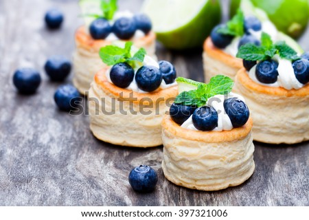 puff  pastry stuffed with soft cream cheese and blueberry with lime on rustic table  - stock photo