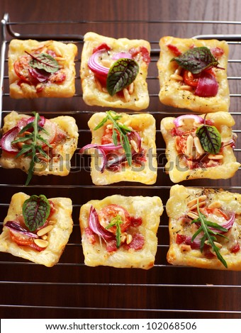 Puff pastry with cheese, tomato and vegetables - stock photo