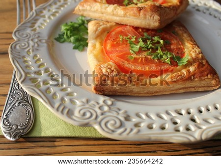 puff pastry with tomatoes, cheese and herbs - stock photo