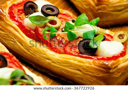 Puff pastry with tomatoes, mozzarella cheese, olives and marjoram - stock photo