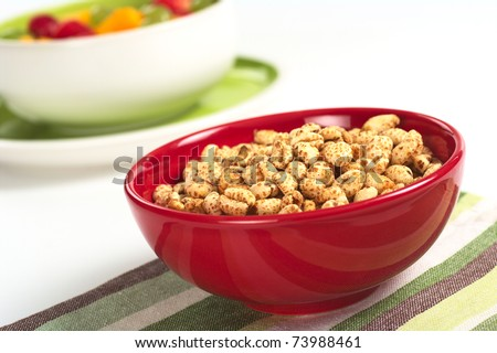 Puffed wheat cereal in red bowl with fruit salad in the background (Selective Focus, Focus on the middle of the cereals) - stock photo