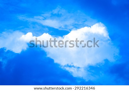 Puffy clouds in a blue mid-summer sky - stock photo