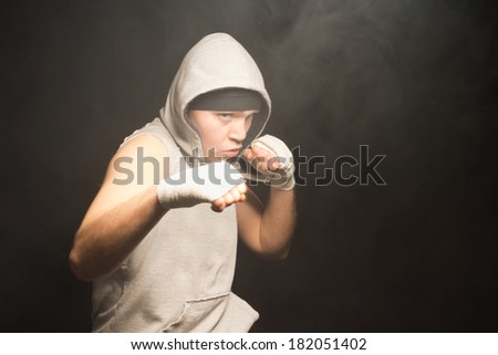 Pugnacious young boxer wearing a hooded top raising his bandaged fists in a fight in a dark smoky atmosphere with copyspace - stock photo