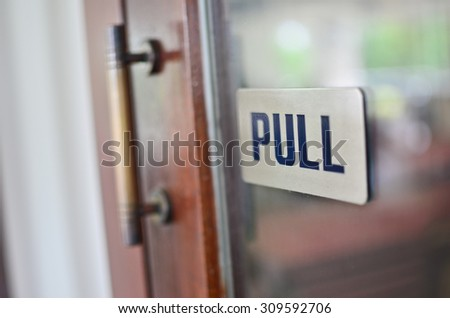 Pull sign on glass door with shallow depth of field